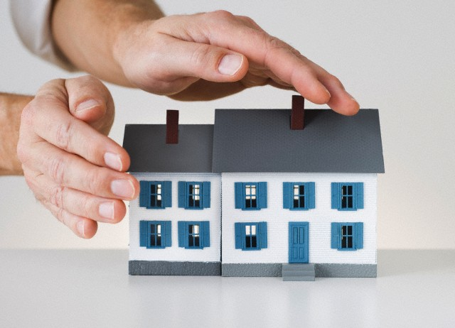 Hands touching toy house --- Image by © Tetra Images/Corbis